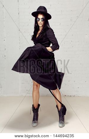 A woman in a black hat, sunglasses and a dress dances, twists its tail, rock'n'roll. Stylish girl in black dress in motion in studio with grey brick wall
