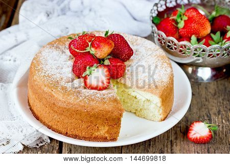 Italian sponge cake pan di spagna with strawberry on old wooden background selective focus