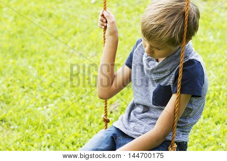 sad lonely boy sitting on swings at outdoor playground. Close up. Sad lonely depressed unhappy mood