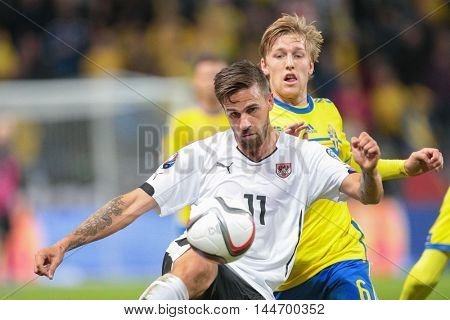 STOCKHOLM, SWEDEN - SEPTEMBER 8, 2015: Martin Harnik (Austria) and Emil Forsberg (Sweden) fight for the ball in an European Championship qualification game.