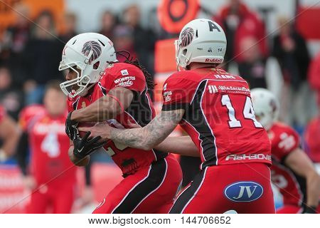 VIENNA, AUSTRIA - April 4, 2016: Grant Enders (New Yorker Lions Braunschweig) hands the ball to Chris Smith (New Yorker Lions Braunschweig). in a game of the Big Six Football League.