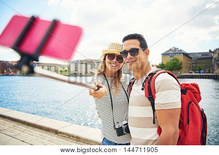 Young couple enjoying a backpacking holiday standing on an urban waterfront of an old town taking a selfie on a mobile phone posing with happy smiles