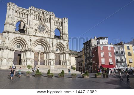 CUENCA SPAIN - APRIL 2 2016: Tourists walk near the facade of the Cuenca's Cathedral The cathedral is dedicated to St Julian gothic english-norman style XII century called the Basilica of Our Lady of Grace, Cuenca, Spain