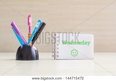 Closeup color pen with black ceramic desk tidy for pen and green wednesday word in white page and normal face emotion at the note book on blurred wood desk and wood wall textured background