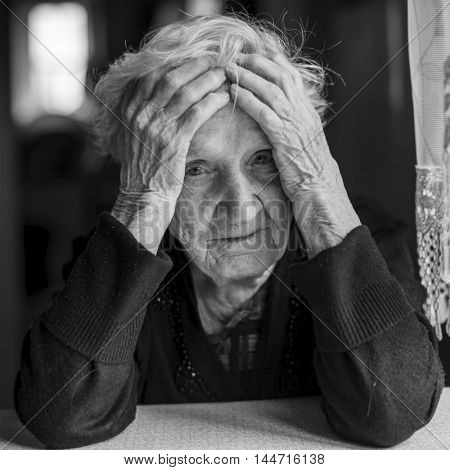 Sad elderly woman holds hands a head. Black and white photo.