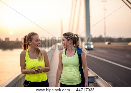 Two attractive female athletes talking together outdoors.
