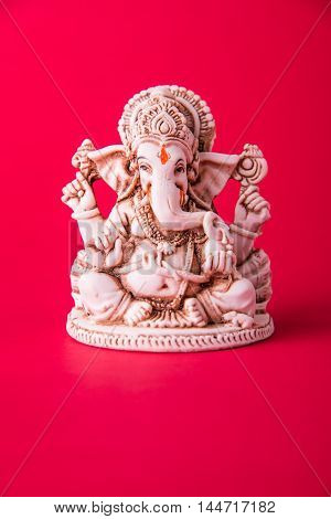statue of Ganesha Idol made of white marbal on plain bright red background. Clear space for text or headline poster