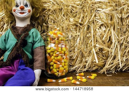 antique porcelain circus clown doll next to glass jar of candy corn with bale of straw background
