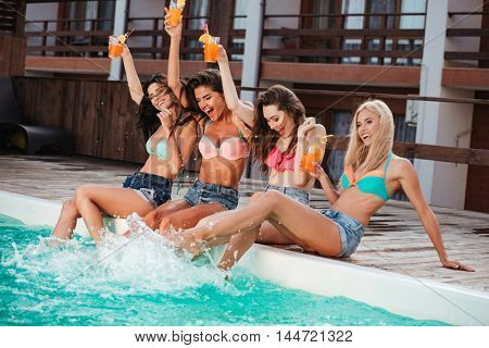 Joyful attractive young women drinking cocktails and having fun near swimming pool