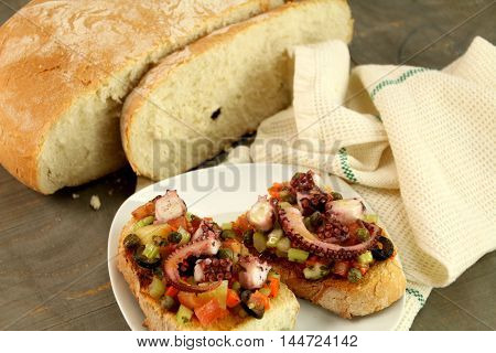 Octopus salad on bruschetta, bread and a cotton dishcloth.