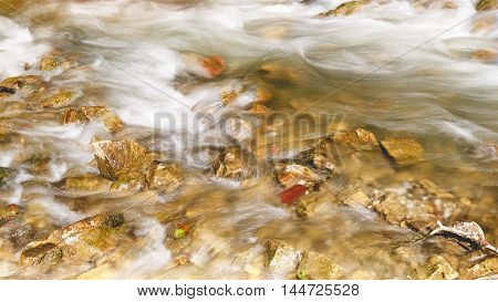 Clear and  rapid mountain river in the summer forest. Long exposure of white water rapids and waves