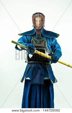 Kendo - Kendoka in full armor with shinai, studio shot on white background.