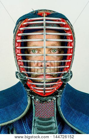 Close up portrait of man in kendo helmet, kendoka studio shot on white.