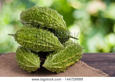 heap of bitter melon or momordica on wooden table with blurred background.