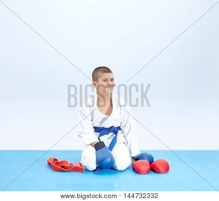 Cheerful athlete in karate pose near karate outfit