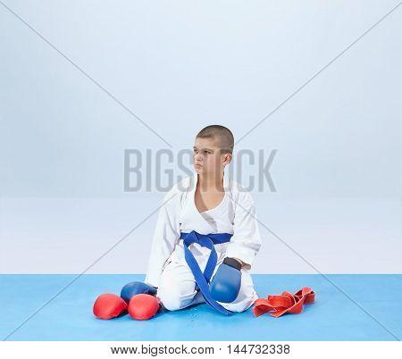 In karategi athlete sits in karate pose near an outfit karate