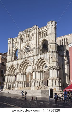 CUENCA SPAIN - APRIL 2 2016: Tourists walk near the facade of the Cuenca's Cathedral The cathedral is dedicated to St Julian gothic english-norman style XII century called the Basilica of Our Lady of Grace