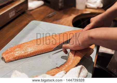 Sushi chef prepares raw fish before service.