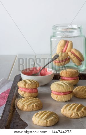 Raspberry Filled Melting Moments on a Baking Tray and in a Jar Vertical