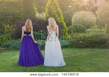 Bride and bridesmaid outside. Two girls posing on the green meadow. Two girls standing back to camera. Bride in wedding dress. Bridesmaid in a purple evening gown.