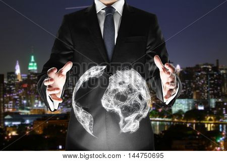 Businessman holding abstract terrestrial globe on illuminated night city background. International business concept