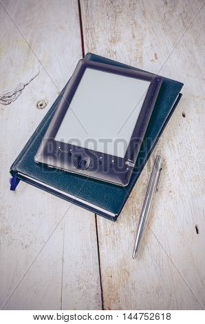 Black ereader with notebook in leather cover and ink pen on vintage old rustic wooden table. Blank E-book reader. New technologies in education. Back to school concept. Selective focus. Copy space.