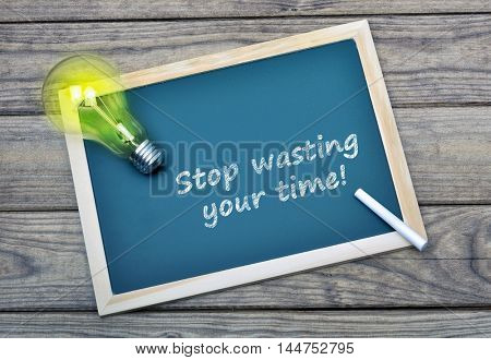 Stop wasting your time text on school board and glowing light bulb