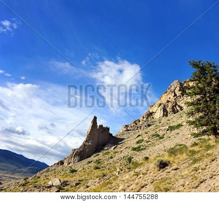 Sandstone monolith stands silouetted against a blue sky in Yellowstone National Park. Other mountains are in the distance.