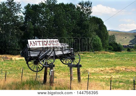 Weathered and rotting wooden wagon sits atop a metal fence. Wagon has a cracked and peeling sign attached with the word antiques on it.