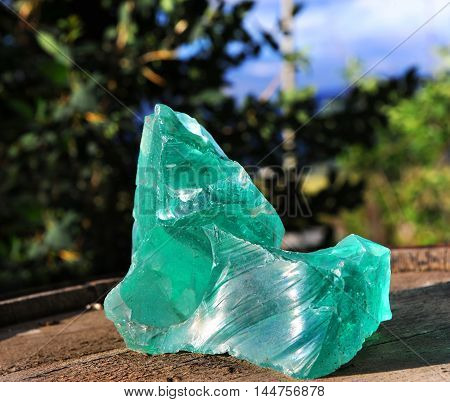 Large turquoise green quartz rock sits on a barrel top in Wyoming.
