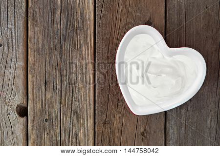 Greek Yogurt In A Heart Shaped Bowl, Downward View Over A Rustic Wood Background