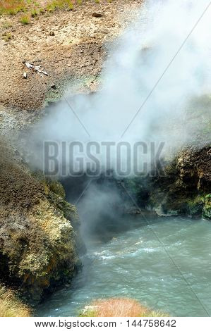Steam and vapors escape landmark known as Dragon's Mouth Spring in Yellowstone National Park. Water boils at entrance to