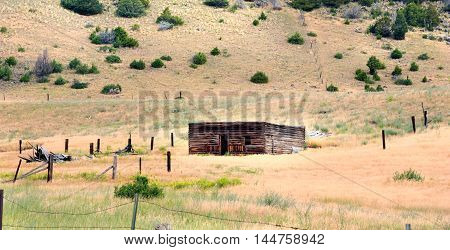 Roofless log cabin is surrounded by old rustic fence. Cabin sits in Happy Valley Wyoming.
