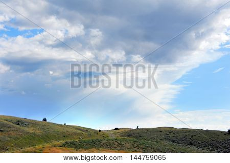 Storm clouds gather on hilltop of the Absaroka Mountains in Montana. Small road tops hill and disappears into clouds.
