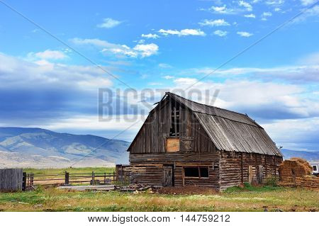 Early morning on a farm in Paradise Valley has a backdrop of mountains and light blue sky. Rustic pole barn has wooden roof and weathered sides.