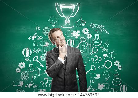 Thoughtful businessman standing against chalkboard with winner's cup and business icons sketch. Business leader concept
