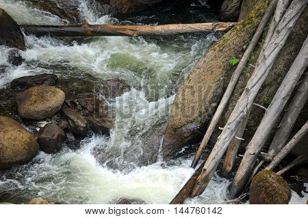 Gibbon River carries fallen trees and logs over Gibbon Falls in Yellowstone National Park.