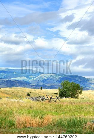 Meadow in Happy Valley Wyoming has view of the Absaroka Mountains. Rustic wooden fence points the way.