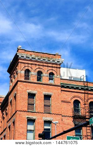 The Bozeman Hotel in Bozeman Montana is Romanesque Revival architecture. Image shows corner of building and arched windows on main street of town. poster