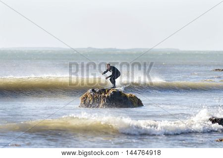 Westport Massachusetts USA - July 5 2014: Surfer off Gooseberry Neck appears to be riding small wave into a rock. Buzzards Bay and Cuttyhunk Island in background.