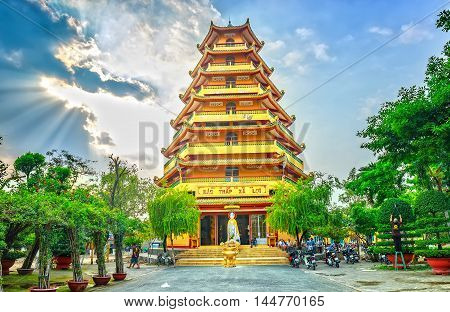 Ho Chi Minh City, Vietnam - January 17th, 2015: The man is pruning bonsai inside stupas in the sunny with sun rays shining down on tower makes warm afternoon