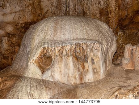 Huge stalagmite in the form of a large mushroom inside the cave.