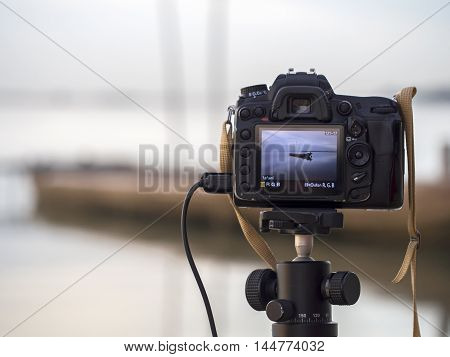 Closeup of a camera on a tripod outdoors. Background Landscape out of focus, select focus