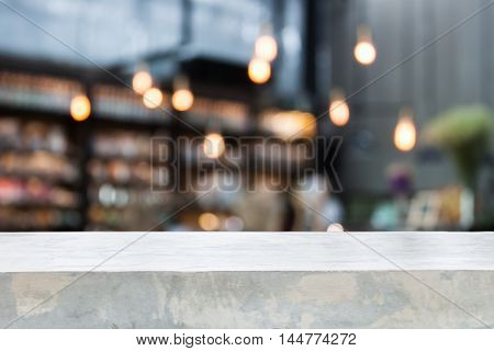 Concrete table top with coffee shop blurred background with bokeh