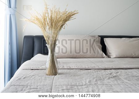 Dried tree rice in a glass bottle flower pot on the bed at bedroom.