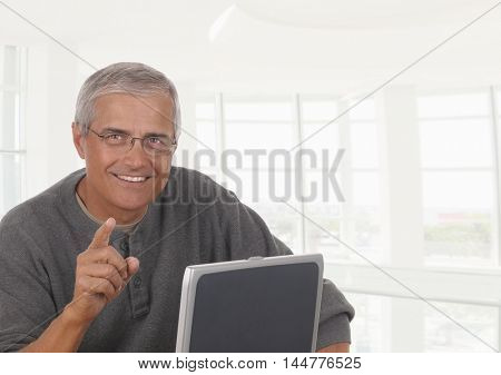 A smiling casually dressed mature businessman seated behind a laptop computer pointing towards viewer.. The man is in front high key office window.