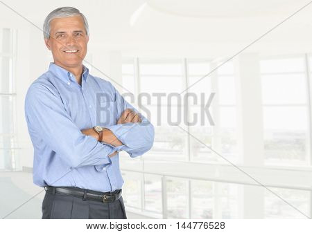 A smiling casually dressed mature businessman standing in front of a large modern office window. High key office background with copy space., copy space Horizontal format.