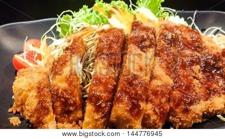 The Crispy Fried Pork And Vegetable With Sauce In Black Plate, Tonkatsu , Japanese Food