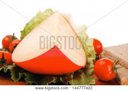 cheese piece on salad with tomato on wood over white