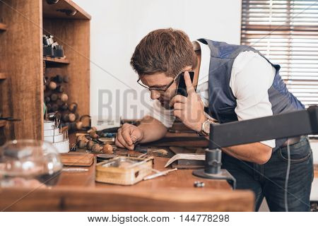 Young jeweler examining a ring and talking on a cellphone while leaning over a workbench full of tools in his shop